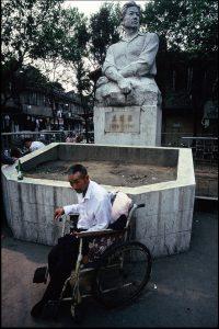 Homme au fauteuil roulant devant une statue